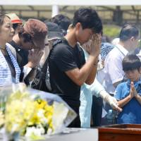Praying for peace: People offer prayers Friday at Nagasaki Peace Park for the victims of the city's 1945 A-bombing. | KYODO