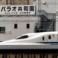 Pacific promo: A bullet train rolls by signs belonging to the Japanese office of Ngeremlengui state in Palau alongside the Tokaido Shinkansen Line near Nagoya Station. | CHUNICHI SHIMBUN