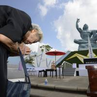 Solemn moment: An elderly woman offers prayers at Nagasaki Peace Park on Friday to mark the 68th anniversary of the atomic attack against the city at the end of World War II. | KYODO