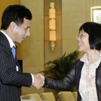 Dialogue: New Komeito member Kyohiko Toyama (left) is greeted by Yang Yanyi, assistant minister of the Chinese Communist Party's International Department, prior to their meeting in Beijing on Monday. | KYODO