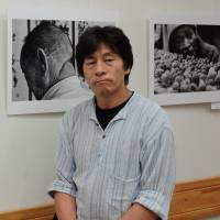 Victims and victimizers: Munesuke Yamamoto stands in front of his photos of survivors of the war at his photo exhibition at a bookstore in Tokyo's Toshima Ward on Aug. 6. | KYODO