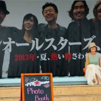 Among the stars: A visitor to the Southern All Stars shop in Chigasaki, Kanagawa Prefecture, takes a photo in front of a huge panel showing the popular group on Aug. 1. | KYODO