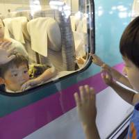 Such sweet sorrow: Two cousins who spent the Bon holidays together part at JR Sendai Station on Saturday as the rush of travelers returning home peaked. | KYODO