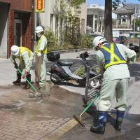 It all falls down: Workers in the city of Kagoshima on Monday clean up ash from Mount Sakurajima following Sunday's volcanic eruption. | KYODO