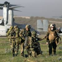 Boots on the ground: U.S. Marines and Ground Self-Defense Force elements alight from MV-22 Ospreys during a joint drill in February in California. | KYODO