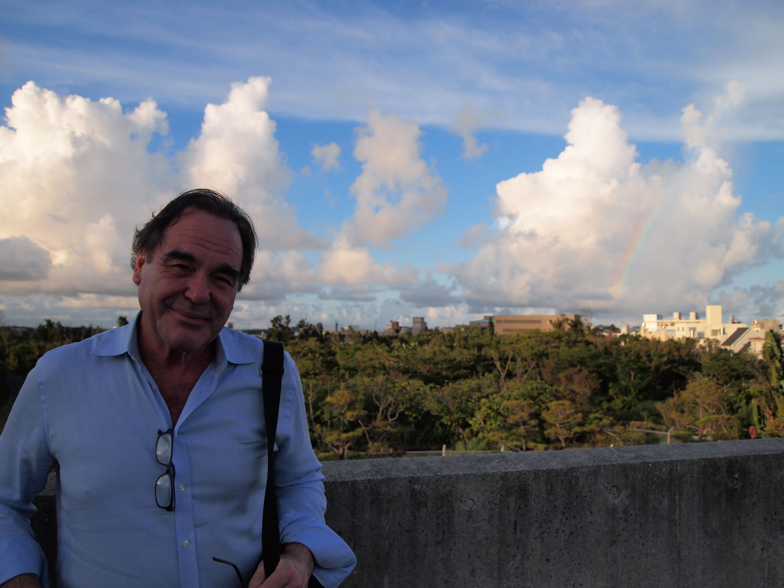 Tour of duty: A rainbow breaks through the clouds as American film director Oliver Stone stands on the rooftop of Sakima Art Museum in Ginowan, Okinawa, on Aug. 13. | JON MITCHELL
