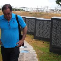 Somber stroll: Oliver Stone walks past granite slabs inscribed with the names of the dead at Peace Memorial Park in Mabuni, Okinawa, on Aug. 14. | JON MITCHELL