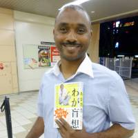 About life: Sudanese national Mohamed Omer Abdin, who is blind, holds his recently published book about his 15-year life in Japan in Tokyo in May. | KYODO