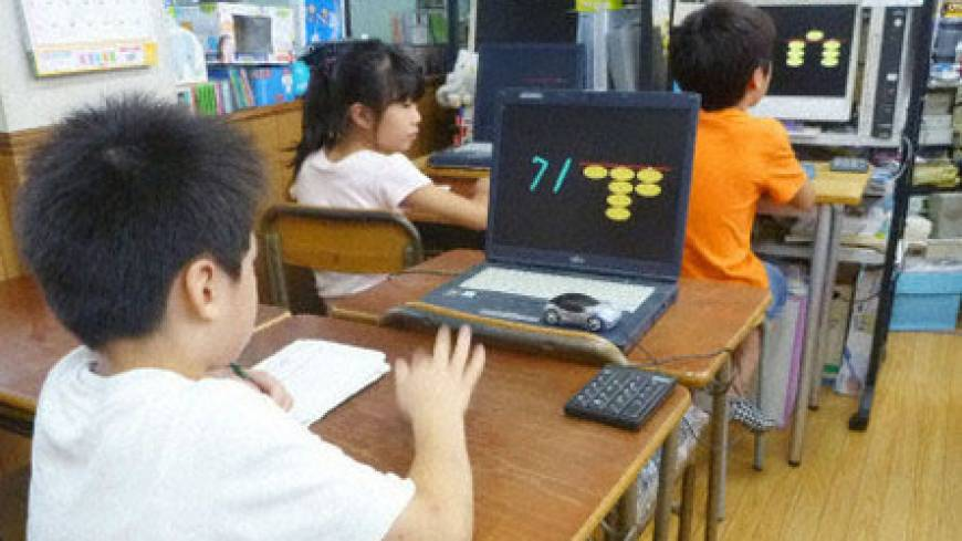 Children practice 'anzan,' or blind calculations, while watching computer screens showing numbers and a scaled-down soroban at a class in Tokyo's Nerima Ward last month. | KYODO