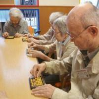 Quick thinking: Senior citizens attend a 'soroban' abacus lesson in Tokyo's Minato Ward in June.    KYODO
