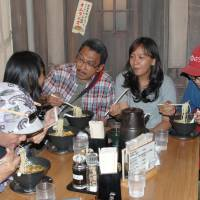 On a high: An Indonesian family eats ramen at the Shinyokohama Raumen Museum, an amusement facility featuring the popular noodles, in Yokohama on Aug. 14. Foreign visitors to Japan in July topped 1 million for the first time, a record high.   KYODO