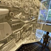 Targeting the nouveau rich: A man walks down a flight of stairs beside a decorated wall adorning the Intersect By Lexus luxury brand experience space run by Toyota Motor Corp., in Tokyo on Friday. | BLOOMBERG