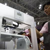 No paper jams: A visitor views 3D Systems Corp.'s CubeX printer at the 3D & Virtual Reality Exhibition in Tokyo in June. | BLOOMBERG