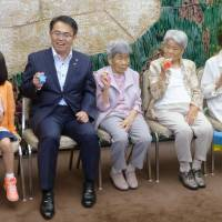 Campaign 'girls': Three daughters of late centenarian Gin Kanie, who with her twin sister, Kin Narita, grabbed national attention until their deaths in the early 2000s, visit Aichi Gov. Hideaki Omura Monday in Nagoya, where they are from. Next month, the daughters will appear in a traffic safety TV commercial produced by the prefecture. | KYODO