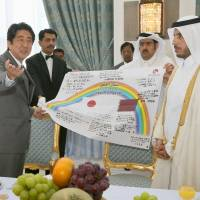 Messenger: Prime Minister Shinzo Abe on Wednesday in Doha presents his Qatari counterpart, Sheikh Abdullah Bin Nasser Bin Khalifa Al Thani, with a banner bearing messages from residents of tsunami-hit Onagawa, Miyagi Prefecture, that thank the people of Qatar for their support in the aftermath of the March 2011 disaster. | KYODO