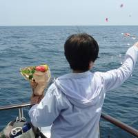 Waving goodbye: A participant in an ash-scattering funeral casts flower petals over the ocean off Manazuru port in Kanagawa Prefecture. | KYODO
