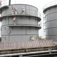 Manning the parapets: Workers are seen on storage tanks at the Fukushima No. 1 power plant in this handout photograph taken during an inspection by the Nuclear Regulation Authority on Aug. 23. | BLOOMBERG