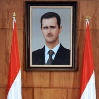 Official response: Syrian Foreign Minister Walid al-Moallem speaks under a portrait of President Bashar Assad during a conference in Damascus on Tuesday.    AFP-JIJI
