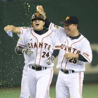 Team excitement: Shuichi Murata (right) celebrates with Yomiuri Giants teammate Yoshinobu Takahashi after the latter's game-ending single in the ninth inning against the Tokyo Yakult Swallows on Thursday at Tokyo Dome. Yomiuri defeated Yakult 6-5. | KYODO