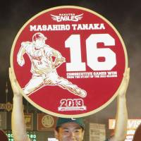 Special recognition: Eagles ace Masahiro Tanaka holds up a commemorative item that displays his record-setting win streak to start the 2013 season. | KYODO