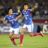 Top of the pile: Shunsuke Nakamura (right) celebrates after one of his two goals against Urawa on Wednesday. | KYODO