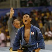 Clean sweep: Masashi Ebinuma celebrates after beating Azamat Mukanov in the men's 66-kg final on Tuesday. | AP
