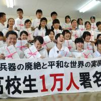 A students' group in Nagasaki Prefecture hold bundles a petitions calling for the abolition of nuclear weapons. | KYODO