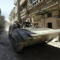 Armored patrol: Syrian troops roll down a deserted street in the central city of Homs on Wednesday. | AFP-JIJI