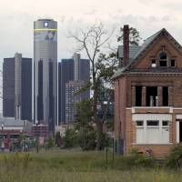 High-rise and fall: Detroit's Renaissance Center (left), the global headquarters of General Motors Co., stands in contrast to a vacant home in the foreground in June. | THE WASHINGTON POST