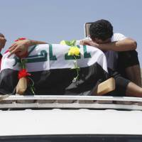 Bride slain: Relatives of an Iraqi killed in a bomb attack during her honeymoon mourn over her coffin in Najaf on Sunday. | AP
