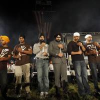 One year later: Family members hold candles Monday during a memorial service at the Sikh  Temple of Wisconsin in Oak Creek to mark the anniversary of a shooting rampage that left six dead. | AP