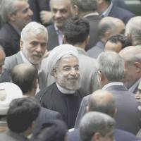 Center of attention: Iranian President Hasan Rouhani leaves at the conclusion of a parliamentary session on his proposed Cabinet on  Tuesday in  Tehran. | AP