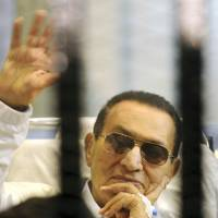 Set to be free: Former Egyptian strongman Hosni Mubarak waves to supporters from behind bars during an April court hearing in Cairo. | AP
