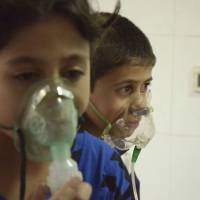 Gas attack: Children affected by what activists say was a gas attack breathe through oxygen masks in the Damascus suburb of Saqba on Wednesday. | REUTERS/KYODO