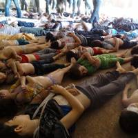 Makeshift morgue: An image released by the Syrian opposition's Shaam News Network shows bodies of children and adults that Syrian rebels claim were killed in a toxic gas attack Wednesday by pro-government forces in Ghouta, a suburb on the outskirts of Damascus. | AFP-JIJI