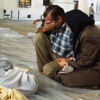 In grief: In this authenticated photo provided by the Local Committee of Arbeen in Damascus, a man and woman mourn over dead bodies Wednesday after an alleged poisonous gas attack perpetrated by pro-regime forces in a suburb of Syria's capital. | AP