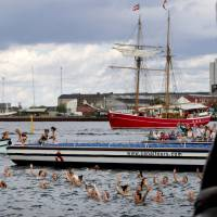 Live counterparts: After jumping off a tour boat, a group of bikini-clad women swim in the shape of the number 100 in the sea in front of the Little Mermaid statue in Copenhagen on Friday. | AP