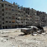 Shattered lives: Heavily damaged buildings stand in Zamalka, a suburb of Damascus, in this image released by the Syrian opposition's Shaam News Network on Aug. 17. | AFP-JIJI
