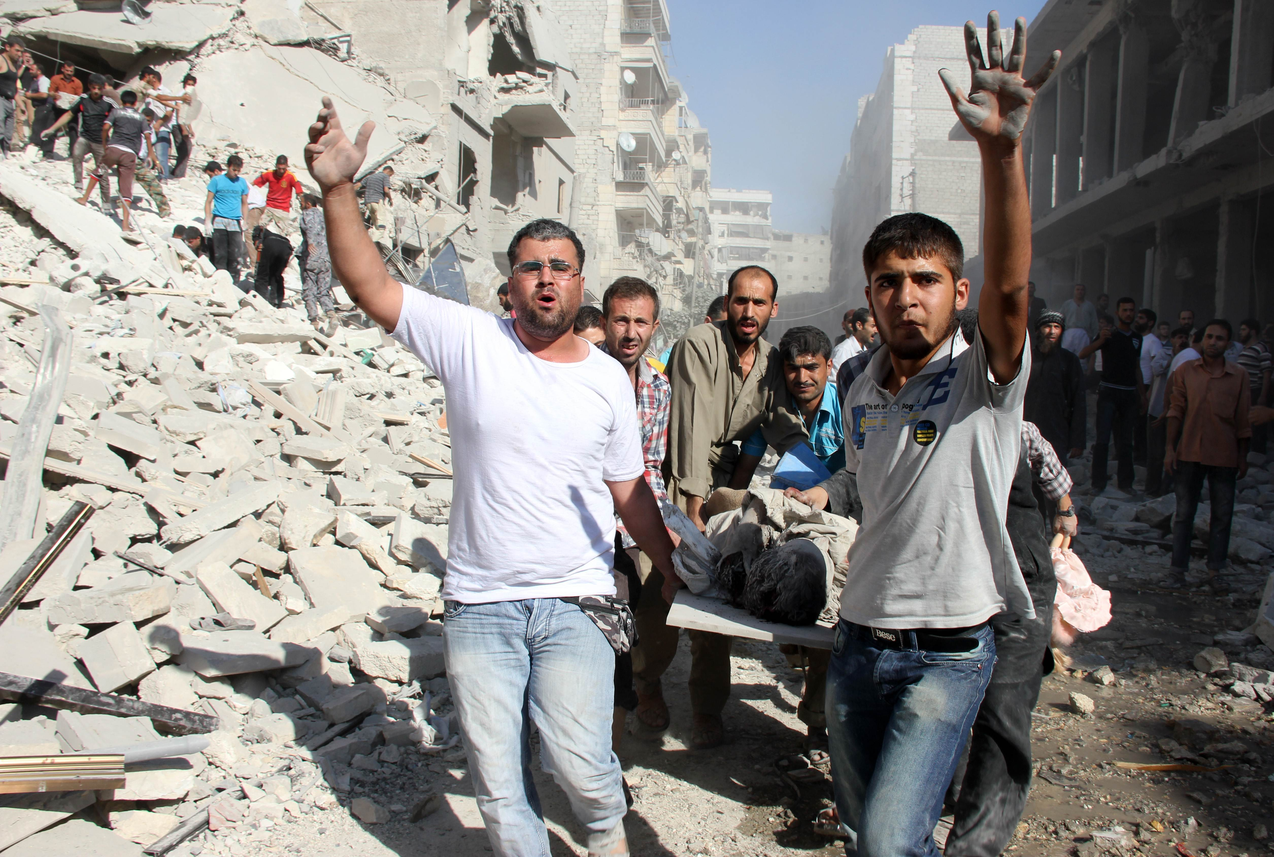Rubble and ruin: Syrians evacuate a victim following an air strike by forces loyal to Syrian President Bashar Assad in Aleppo on Monday. | AFP-JIJI