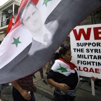 Expat excoriation: A members of the Syrian community in Allentown, Pennsylvania, holds a flag with a portrait of President Bashar Assad on Friday during a march in protest of a potential U.S. strike against the regime. | AP