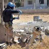 Gathering evidence: A member of a U.N. investigation team takes samples of sand Wednesday near the remains of what is believed to be one of the rockets containing deadly chemicals that were launched by the Syrian regime in the Damascus suburb of Ain Terma. | AP