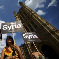 No more blind trust: Demonstrators protest the prospect of British military involvement in Syria outside of London's Houses of Parliament on Thursday. | AFP-JIJI