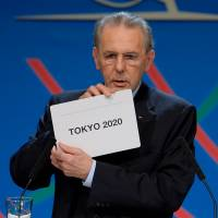 International Olympic Committee President Jacques Rogge shows a card displaying Tokyo, the city  chosen to host the 2020 Summer Olympics, in Buenos Aires, Saturday. | AP