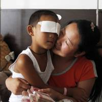 Hope: Guo Bin, whose eyes were gouged out Aug. 24, sits with his mom in Taiyuan, China, on Tuesday. | AFP-JIJI