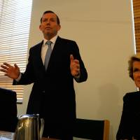 New man: Australian Prime Minister-elect Tony Abbott (center) speaks to newly elected members along with the deputy leader of the Liberal Party, Julie Bishop (right), and National Party leader Warren Truss at Parliament House in Canberra on Friday. | AFP-JIJI