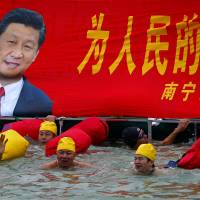 All-seeing: A swimmer waves near a banner with a portrait of new Chinese leader Xi Jinping in Nanning, in southern Guangxi Zhuang Autonomous Region, in January. | AP
