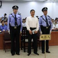 Defiant to the end: Chinese politician Bo Xilai, who was tried last month on charges of taking bribes, embezzlement and abuse of power, stands in court in Jinan, Shandong province, on Sunday, where he was sentenced to life in prison. | AP