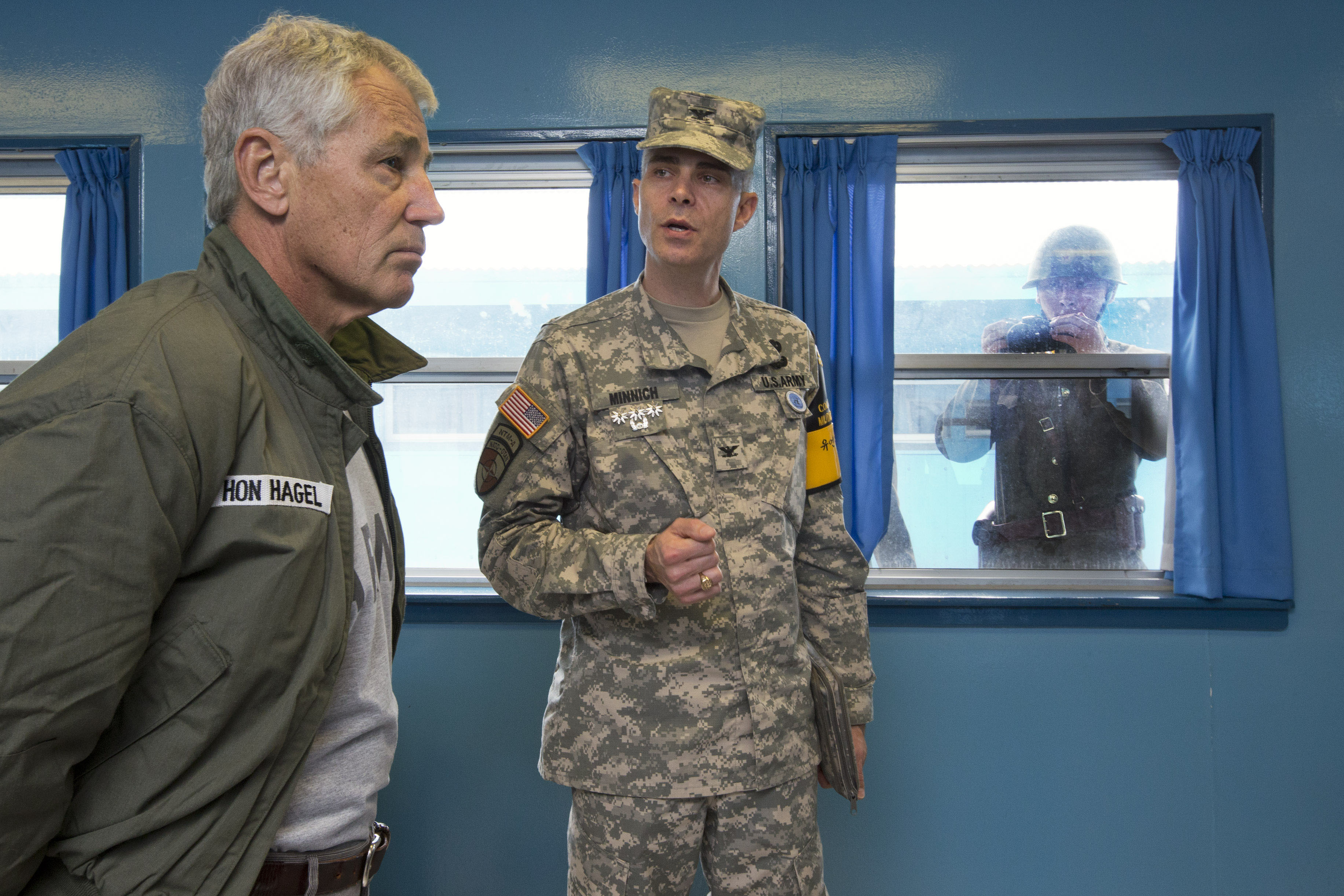 Picture this: U.S. Secretary of Defense Chuck Hagel (left) listens to U.S. Army Col. James Minnich as a North Korean soldier takes a photograph of them through the window of a building at the demilitarized zone in Panmunjom, South Korea, on Monday. | AP