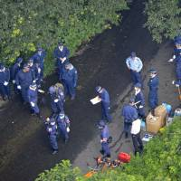 Grim discovery: Investigators gather at a crime scene in Kure, Hiroshima Prefecture, after the body of a 16-year-old girl was discovered. | KYODO