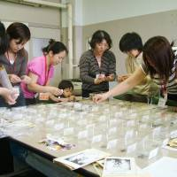 For whom the bell doles: Mothers sort 'bell mark' coupons brought from home by students at Akabanedainishi Elementary School in  Tokyo's Kita  Ward.  The symbols found on certain products can be cashed in for donations to schools. | KYODO